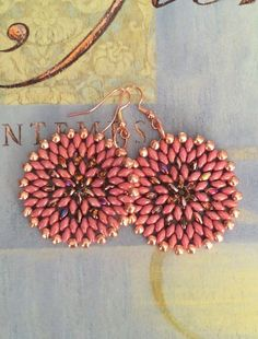 Bold, bright disk earrings created with a beautiful rosey mauve mixed with metallic copper beads. These beautiful beads are woven to make these
