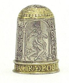 Decidedly upmarket and un-Puritan silver-gilt thimble with scenes of an erotic nature. via V&A website where said to be English c.1600. Inscribed LA PVISSANCE D'AMOVR DESIRE N'A MON REPOS [the power of love; my desire has no rest] -- very much in tune with the late 16C engraved designs for thimbles of Theodor de Bry -- see previous