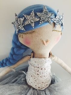 READY FOR HER NEW HOME.Handmade cloth doll with pale blue hair in a long side plait.Wearing a white cotton embroidered top with a silver tulle skirt and grey sparkly knee socks.With a sparkly star crown.All clothes are removable.Each doll is hand dyed in tea  to create variations in skin tones and stuffed with eco friendly fibre stuffing. They are all made of cotton and clothed in new and recycled fabrics and findings.All seams are double stitched for extra strengt...