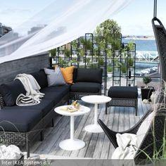 Die Sitzecke auf der Terrasse besteht aus schwarzen Rattanmöbeln mit schwarzen Polstern und einem hängenden Lounge-Sessel. Unter einem flatternden Baldachin lässt …
