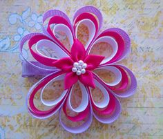 Loopy ribbon flower hair bow in purple, pink and white with a pink flower embellishment in the centre. The hair bow measures approximately Flower Hair Bows, Baby Hair Bows, Flowers In Hair, Fabric Flowers, Ribbon Flower, Baby Hair Accessories, Hair Bow Tutorial, Ribbon Hair Bows, Making Hair Bows
