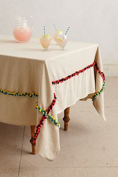 Nomades Table Linen #anthropologie Buy a drop cloth for painting about $10 and add pompom balls and there you go!!