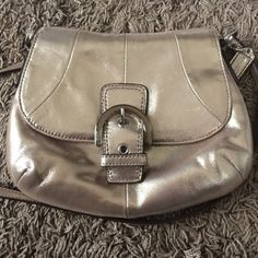 COACH METALLIC MINI CROSS BODY Used in great condition. This is a reposh. There are scratches and marks on the front and back but it's hard to tell with the metallic material. I pictured the most noticeable. The strap has creasing. The inside is in good condition but it does have staining no tears. There is also some creasing in the front flap. I have many more coach items in my closet as I am selling my collection. If you are interested in more than one item let me know. I'll give you a…