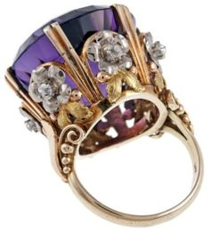 A huge, deep purple amethyst set in a gold ring with diamond flowers.  Victorian - circa 1880.