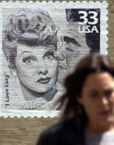 "A pedestrian walks in front of a large mural of an ""I Love Lucy"" stamp on the post office near the Lucy-Desi Museum in Jamestown, N.Y., May 3, 2002. Jamestown is Lucille Ball's hometown."