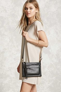 An unstructured faux leather handbag featuring a zipper top, front zipper pocket with a storm flap, a removable adjustable crossbody strap, and high-polish accents.