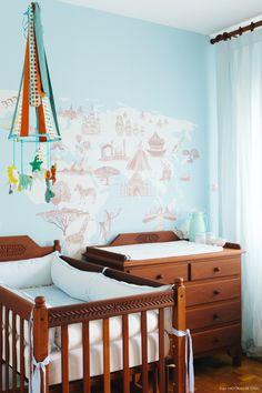 Quarto de bebê com papel de parede de mapa mundi e cortina de linho azul claro.
