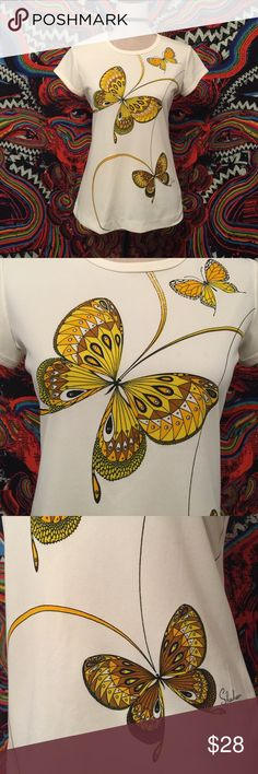 Vintage 70's Retro Mod Butterfly Tee This adorable shirt from the 70's is from my own personal collection! By Miss Shaheen. Labeled as a size 8 but fits like a modern M. 100% Poly creamy ivory tee with a vibrant butterfly graphic, ringer cap sleeves and neckline. In very good condition. Has some slight discolorations front left that are hardly visible and a few slight spots on the left sleeve that again, are hardly noticeable. Still has lots of life left in it! Measurements (taken flat)…