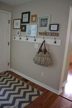 hooks with mismatched picture frames and welcome sign