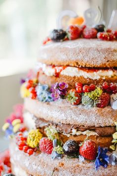 3-tier naked sponge wedding cake decorated with summer flowers and berries.
