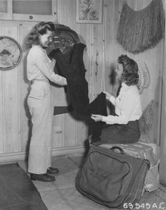 A Flight Nurse proudly displays her black nightgown to another nurse who appears to be 2nd Lt. Emma A. Raspet (see the name on the suit bag). Kwajalein, Marshall Islands.