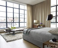 In the grey-and-tan master bedroom of a TriBeCa apartment, the bed is by Meridiani, the wall lamp is by Serge Mouille and the vintage Poul Kjaerholm daybed retains its original leather. The side table is by Wyeth and the console is a vintage piece by Paul McCobb. The circa-1970 Beni Ourain rug is from Double Knot.