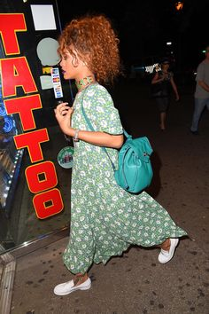 Rihanna in a floral print maxi, turquoise backpack, and white loafers