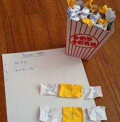 Mathe-Popcorn: Zahlen auf weißen Zetteln und Rechenzeichen auf gelben Zetteln.