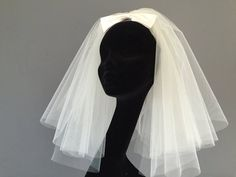 $74 This 60s style Bouffant veil for anyone rocking the 60s retro look for their wedding.  This short veil is made fuller than our other short layered veils, 2 full circles, of warm Ivory tulle which measure approx 15 (38cm) and 17 (43cm) to give it the 60s look. Great for bride with winged eyeliner or channeling their inner Priscilla. A large silk Ivory bow finishes off the veil measuring just over 5 ( 12.7cm) long for a very cool, retro look.