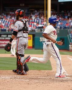 Philadelphia Phillies' Ben Revere, right, scores a run on the hit by Chase Utley as San Francisco Giants catcher Buster Posey, left, looks back to the field during the fifth inning of a baseball game, Thursday, July 24, 2014, in Philadelphia. (AP Photo/Chris Szagola)