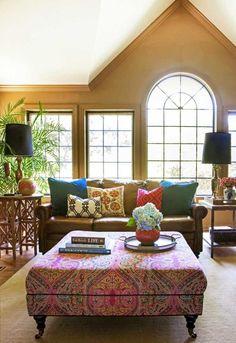 coussins multicolores à motifs originaux et ottoman rose à motifs baroques dans le salon bohème