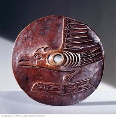 Salish. Spindle whorl, used by the Coast Salish during spinning to prevent the wool slipping from the spindle. Carved in relief with a thunderbird and whale design. Museum no. 9846 Country of Origin: Northwest Coast of America. Culture: Salish. Date/Period: collected 1912. Place of Origin: Lower Fraser River. Material Size: wood.