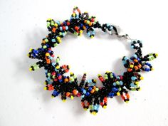 This bracelet is fu-u-un to wear! It has a tribal feel because of the colors and shapes. It consists of a lovely beaded spiral made from black and
