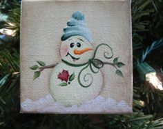 This listing is for a hand painted snowman ornament that is painted on a mini square canvas which measures 2-3/4 inches by 2-3/4 inches. This adorable snowman is painted on a background of light tan with tree branches for arms...a simple heart on her chest and a pink and white hat on her head! A pink bow adds a finishing touch for her scarf. There is snow on the ground and I have added a brown checkers around the sides of the canvas to give it just a little extra detail.  This canvas…