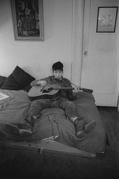 Playing harmonica and guitar in his apartment
