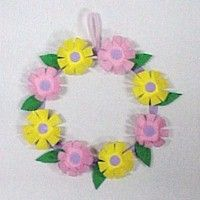 Cute Egg Carton Wreath is made from pink and yellow egg carton sections,  white poster board and green construction paper.