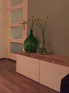 Ikea besta tv-meubel met steigerhouten plank. Gistingsflessen met bloemen.