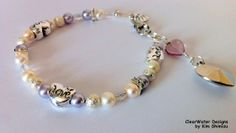 "Silver Heart Pearl Bracelet Freshwater by ClearWaterDesignsbyK, $23.67 http://clearwaterdesignsbyk.etsy.com http://clearwaterdesigns.info This pretty White Pearl Bracelet has Silver Alloy Heart Shaped Beads that say ""Love"" on them. This lovely romantic bracelet would make a great Valentine's Day Gift, Bridal Jewelry or Bridesmaid's Gift. This bracelet is accented with Silver Filled Stardust beads, Mauve Swarovski Pearls & a Silver Toned Acrylic Heart Charm."