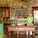 This kitchen gets its distinctive look primarily from its location, at the base of a windmill tower on an old sugarcane plantation in the Caribbean. Recreate a similar island effect with natural wood pieces, lush vegetation, and bold floral accents in tropical shades of red, blue, and green.