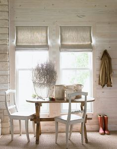 White, intimate dining area for two. Found on the House Beautiful website. White chairs mixed with the warm wood of the table and the white washed or pickled walls. Modern farmhouse or Scandinavian inspired. The windows maximize the light from outdoors. Linen Roman Shades, Rustic Roman Shades, Farmhouse Roman Shades, Wood Wall Design, Whitewash Wood, Decorating Small Spaces, Window Coverings, Farmhouse Style, Modern Farmhouse