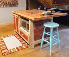 This kitchen island was made from reclaimed-barn-wood! All the wood was salvaged (for free!) from local farms: that barn-red base is the real deal. The countertop was constructed using plants cut from old rafters.