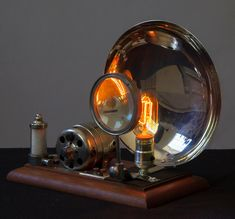 Steampunk Magnilight. Desktop light made with magnifying glass and large chrome reflector. The vintage style bulb really makes an interesting pattern on the reflector. The mount is an old dental vacuum pump.