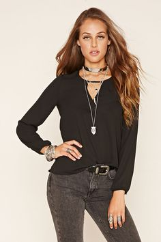 A semi-sheer woven top featuring a front V-cutout, round neckline, and long buttoned cuff sleeves.
