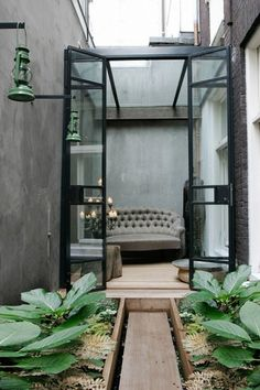 テラスに作られたガラス張りの温室の屋外リビング