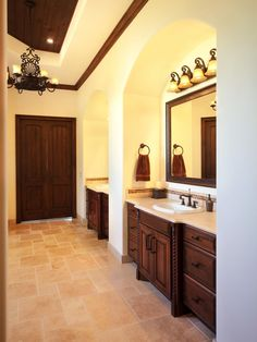 Each wood vanity has an arched niche in this spacious master bathroom. A metal chandelier adds elegance and additional lighting to the double vanities.