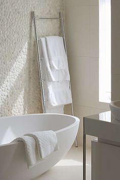 Stone wall in the bathroom. I like the towel rack