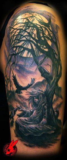 Dead tree crow tattoo on a man's arm