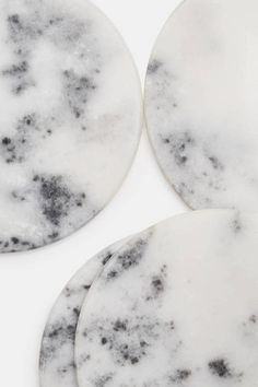 Tenfold New York transcends typical homegoods in favor of the exquisite and the enduring. The collection's marble items are crafted in India and include this set of four coasters. Each smooth disc reflects the unique striations and natural veining of the metamorphic stone. Cork pads on the bottom protect surfaces from scratching.