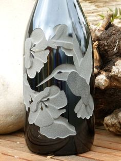 Hummingbird Design is carved / sandblasted onto empty wine bottle and transformed into either an oil lamp or oil dispensor.