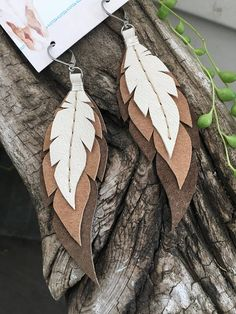 Handcrafted leather wrapped and sewn earrings. Each feather is individually cut and sewn by me. They hang on stainless steel earwire (see photo) and are approximately 4 long. Three delicate layers in dark brown, sand, and cream. Fantastically lightweight and fun! Due to the nature