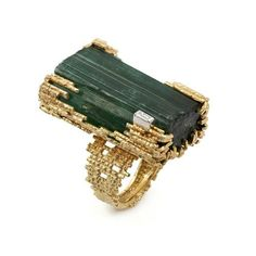 Andrew Grima  Tourmaline Crystal Ring, circa 1969  A large Tourmaline Crystal set in Yellow Gold textured wire and one baguette-cut Diamond.