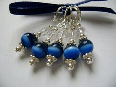 Set of 5 stitch markers made from midnight cats eye glass beads, set off by Swarovski crystal beads, tiny silver seed beads, silver daisy spacer beads and silver plated jump rings/lobster clasps. Can be purchased to fit 4mm, 6mm, 7mm knitting needles or with lobster clasps for crochet. Please choose option when purchasing. These stitch markers will come tied with a ribbon and with their own organza bag to keep them safe when not in use.
