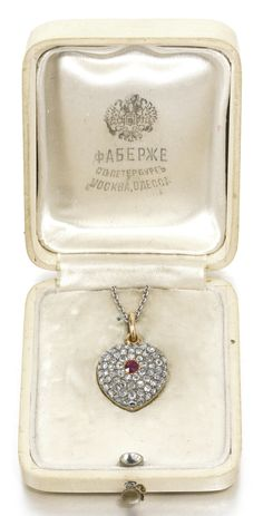 A Fabergé jeweled gold pendant locket, workmaster August Holmström, St Petersburg, 1899-1904, in the form of a heart, the front pavé set with rose-cut diamonds centring a circular-cut ruby, pendant loop.
