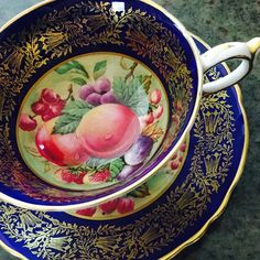 Stuning Paragon Orchard Fruit cup and saucer with navy band and gold design surrounding beautiful fruits. In very good condition, no chips, cracks or repairs. Measures: Cup 2 1/4 high & Saucer Measures 5 1/2 diameter