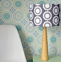 This stunningwooden table lamp is hand crafted in North East England. The handmade drum lampshade in a floralScandinavian inspired design in grey is fitted to