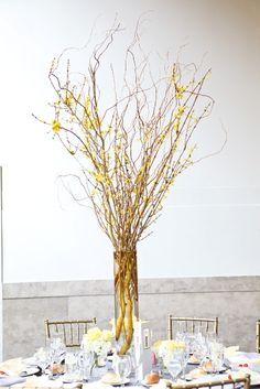 a stark, modern centerpiece off forsythia branches with tiny vases of yellow roses on the table. Yellow and Grey at The Mezzanine in Newark, NJ. This wedding was eatured on Style me Pretty!