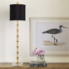 Add instant glamour to your buffet or entry console. The casual bamboo motif gets dressed up in a gold-leaf finish. Lamp rests on a crystal glass square base and is paired with a black shade for a modern touch.