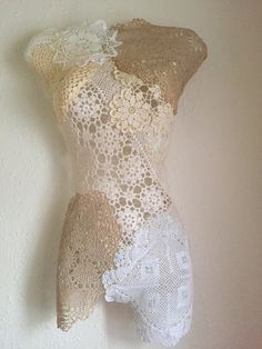 Doily mannequin art. I created this using a half mannequin that I wrapped in clingfilm, I then used a paintbrush and glue to apply the doilies. Was very easy to remove once dry and used two simple tacks to hang on the wall.
