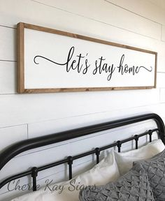 Lets stay home sign, farmhouse bedroom sign (pictured above a queen size bed) » size 1 x 4 appx. » painted lettering » background color: white » lettering color: black » frame color: brown » this sign is able to be hung by the frame » Our signs are made for interior decorating; no