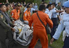 Indonesian Air Force personnel carry airplane parts recovered from the water near the site where AirAsia Flight 8501 disappeared, at the airbase in Pangkalan Bun, Central Borneo, Indonesia, Tuesday, Dec. 30, 2014. Bodies and debris seen floating in Indonesian waters Tuesday, painfully ended the mystery of AirAsia Flight 8501, which crashed into the Java Sea and was lost to searchers for more than two days. (AP Photo/Dewi Nurcahyani)